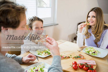Family eating pizza and salad at home Stock Photo - Premium Royalty-Free, Image code: 6121-07809851