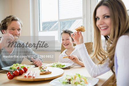 Family eating pizza and salad at home Stock Photo - Premium Royalty-Free, Image code: 6121-07809852