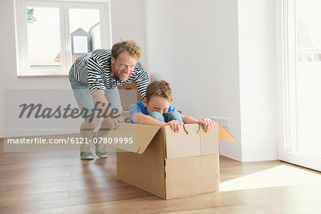 Father son new apartment playing cardboard box Stock Photo - Premium Royalty-Free, Image code: 6121-07809995