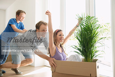 Family moving in home new house playing boxes Stock Photo - Premium Royalty-Free, Image code: 6121-07810002