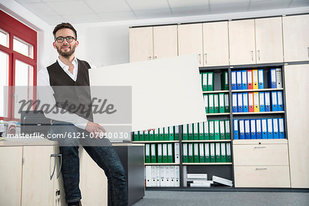 Young man office holding poster sign advert Stock Photo - Premium Royalty-Free, Image code: 6121-07810030