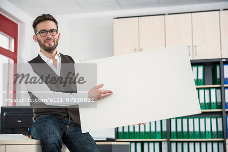 Young man office holding poster sign advert Stock Photo - Premium Royalty-Free, Image code: 6121-07810031