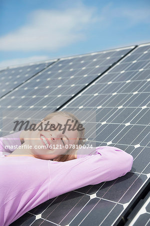 Relaxing happy green energy girl solar panel Stock Photo - Premium Royalty-Free, Image code: 6121-07810074