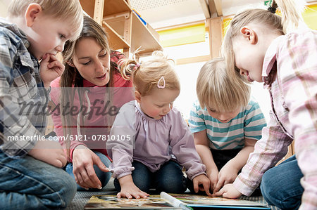 Female educator and four kids looking at picture book Stock Photo - Premium Royalty-Free, Image code: 6121-07810105