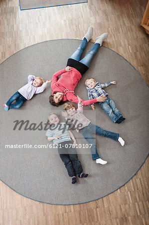 Female educator and four kids relaxing on ground in kindergarten, elevated view Stock Photo - Premium Royalty-Free, Image code: 6121-07810107