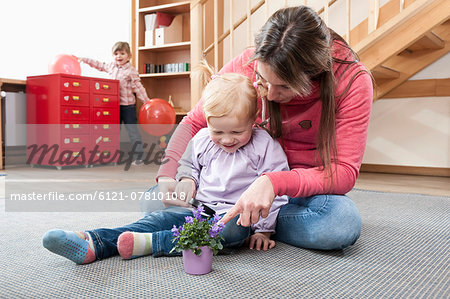 Female educator playing with little girl in kindergarten Stock Photo - Premium Royalty-Free, Image code: 6121-07810108