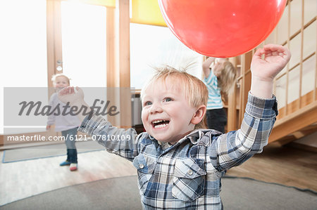 Kids playing with red balloons in kindergarten Stock Photo - Premium Royalty-Free, Image code: 6121-07810109
