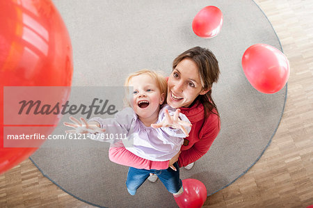 Female educator and little girl playing with red balloons in kindergarten Stock Photo - Premium Royalty-Free, Image code: 6121-07810111
