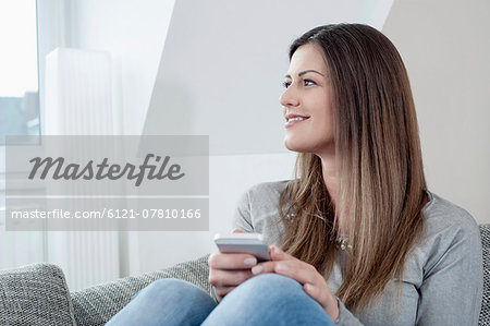 Portrait of smiling young woman with smartphone sitting on couch at home Stock Photo - Premium Royalty-Free, Image code: 6121-07810166