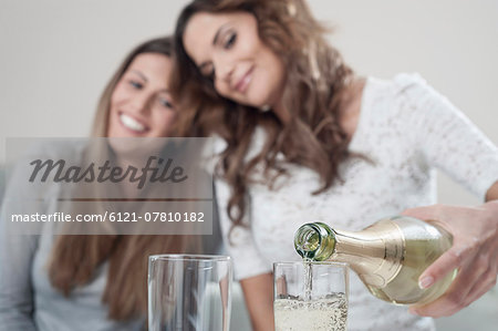 Young woman pouring champage into glasses while her female friend watching Stock Photo - Premium Royalty-Free, Image code: 6121-07810182