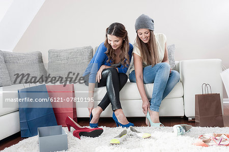 Two young female friends sitting side by side on couch at home trying on high heels Stock Photo - Premium Royalty-Free, Image code: 6121-07810195