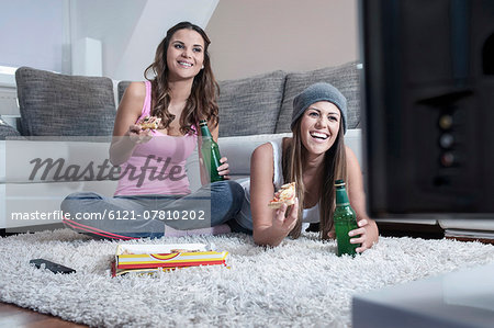 Two female friends side by side on carpet at home watching television Stock Photo - Premium Royalty-Free, Image code: 6121-07810202