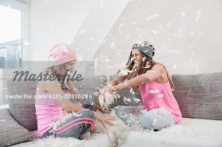 Two female friends sitting on couch at home having pillow fight Stock Photo - Premium Royalty-Free, Image code: 6121-07810206