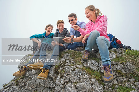 Father teenage kids sitting on rocks using iPad Stock Photo - Premium Royalty-Free, Image code: 6121-07810257
