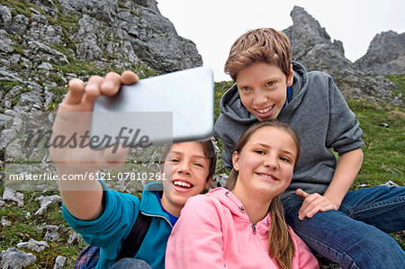 Girl and teenage boys self-portrait cell phone Stock Photo - Premium Royalty-Free, Image code: 6121-07810261