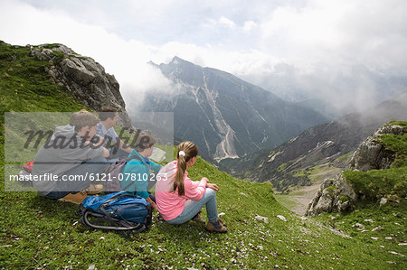 Father and kids looking at hiking map mountains Stock Photo - Premium Royalty-Free, Image code: 6121-07810263