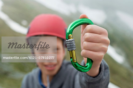 Young boy helmet holding climbing Carabiner Stock Photo - Premium Royalty-Free, Image code: 6121-07810277