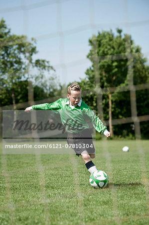 Young boy soccer penalty practice football ball Stock Photo - Premium Royalty-Free, Image code: 6121-07810304