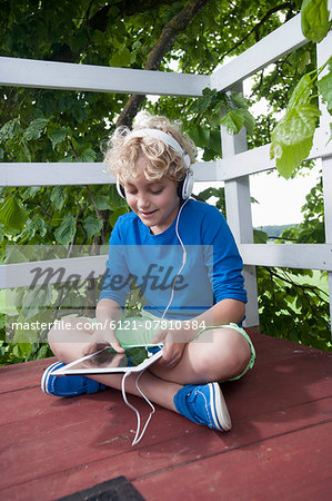 Boy sitting tree-house tablet computer headphones Stock Photo - Premium Royalty-Free, Image code: 6121-07810384