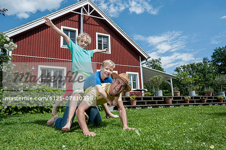 Father and sons playing in garden house Stock Photo - Premium Royalty-Free, Image code: 6121-07810395