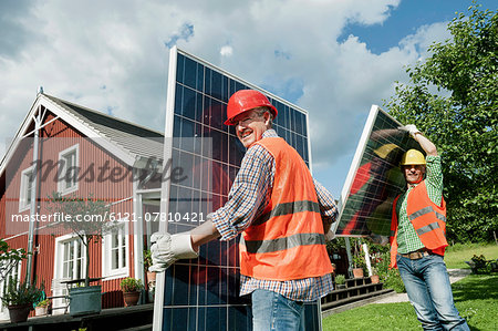 Two workmen installing solar panel house Stock Photo - Premium Royalty-Free, Image code: 6121-07810421