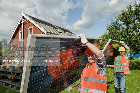 Workmen delivering solar panel house garden Stock Photo - Premium Royalty-Free, Image code: 6121-07810422