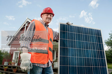Close up portrait man holding solar panel Stock Photo - Premium Royalty-Free, Image code: 6121-07810428