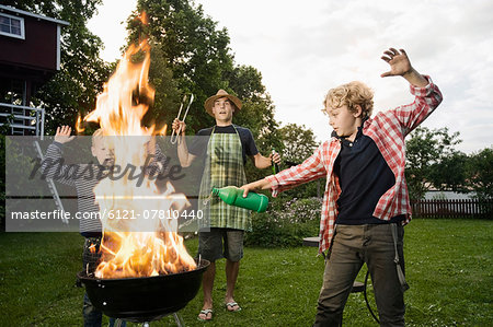 Boy pouring methylated spirit on barbecue fire Stock Photo - Premium Royalty-Free, Image code: 6121-07810440