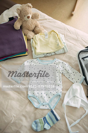 Still life baby clothes bed teddy bear packing Stock Photo - Premium Royalty-Free, Image code: 6121-07970016