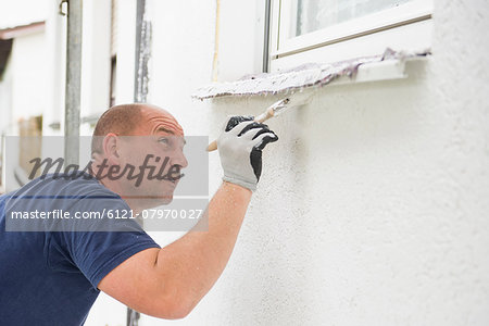 Man alone painting brush window wall house Stock Photo - Premium Royalty-Free, Image code: 6121-07970027