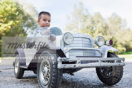 Small boy sitting driving model vintage car Stock Photo - Premium Royalty-Free, Image code: 6121-07970118