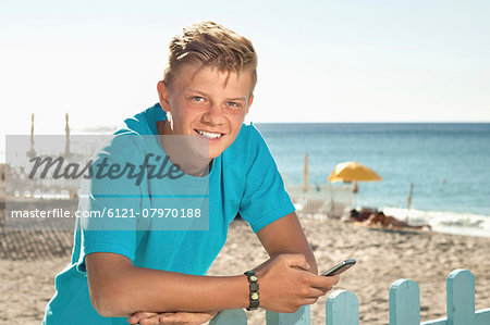 Teenager beach summer holiday fence mobile phone Stock Photo - Premium Royalty-Free, Image code: 6121-07970188
