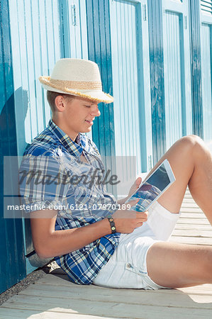 Teenager reading holiday beach summer straw hat Stock Photo - Premium Royalty-Free, Image code: 6121-07970189
