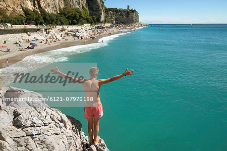 Teenager boy cliff holiday ocean waiting adventure Stock Photo - Premium Royalty-Free, Image code: 6121-07970198