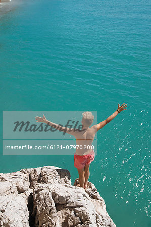 Boy cliff diving holiday ocean sunshine summer Stock Photo - Premium Royalty-Free, Image code: 6121-07970200