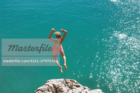 Teenager water cliff sunshine summer holiday jump Stock Photo - Premium Royalty-Free, Image code: 6121-07970201