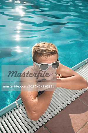 Boy swimming pool sunglasses holiday relaxing Stock Photo - Premium Royalty-Free, Image code: 6121-07970215