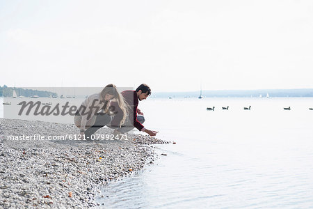 Young couple lake shore gathering pebbles Stock Photo - Premium Royalty-Free, Image code: 6121-07992471