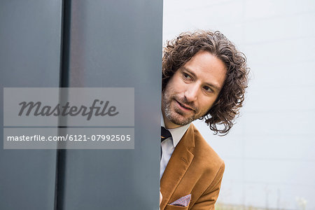 Portrait man close up wall curious looking hiding Stock Photo - Premium Royalty-Free, Image code: 6121-07992505