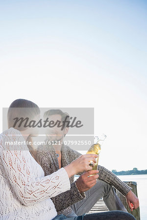 Young man woman sitting jetty drinking beer Stock Photo - Premium Royalty-Free, Image code: 6121-07992550