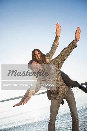 Young couple woman riding piggyback sunset Stock Photo - Premium Royalty-Free, Image code: 6121-07992555