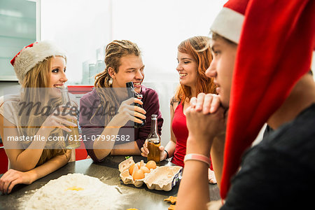 Group of friends preparing cake and drinking beer on Christmas Eve, Munich, Bavaria, Germany Stock Photo - Premium Royalty-Free, Image code: 6121-07992582