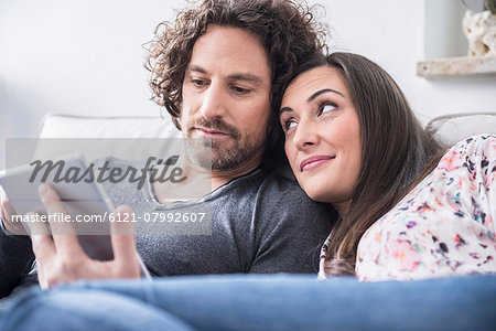 Couple using a digital tablet at home, Munich, Bavaria, Germany Stock Photo - Premium Royalty-Free, Image code: 6121-07992607