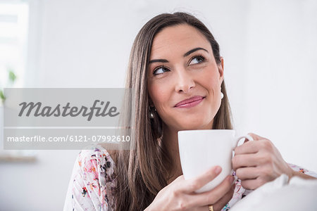 Beautiful woman drinking cup of coffee at sofa, Munich, Bavaria, Germany Stock Photo - Premium Royalty-Free, Image code: 6121-07992610