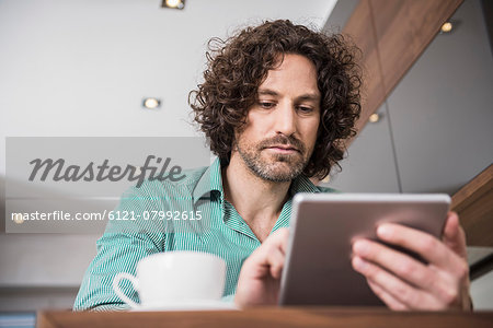 Man using a digital tablet in a kitchen, Munich, Bavaria, Germany Stock Photo - Premium Royalty-Free, Image code: 6121-07992615