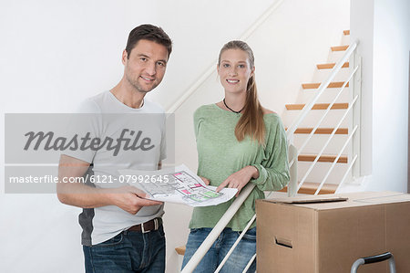 Couple discussing a blueprint by staircase in new home, Bavaria, Germany