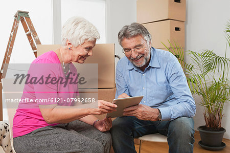 Senior couple using a digital tablet in new apartment, Bavaria, Germany Stock Photo - Premium Royalty-Free, Image code: 6121-07992658