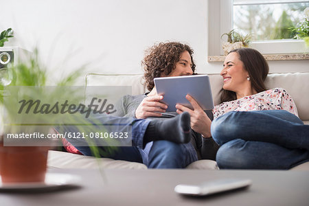 Couple using digital tablet at home, Munich, Bavaria, Germany Stock Photo - Premium Royalty-Free, Image code: 6121-08106523
