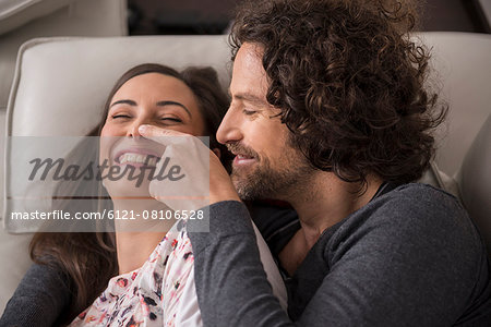 Mid adult couple lying on sofa and smiling, Munich, Bavaria, Germany Stock Photo - Premium Royalty-Free, Image code: 6121-08106528