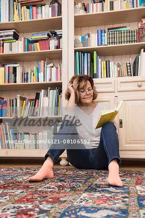 Senior woman sitting on the floor in front of bookshelf and reading, Munich, Bavaria, Germany Stock Photo - Premium Royalty-Free, Image code: 6121-08106592